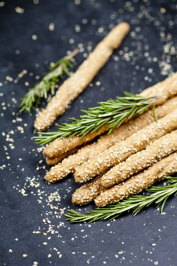 Italian grissini bread sticks with sesame and rosemary herb on b