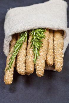 Italian grissini bread sticks with rosemary herb on linen napkin