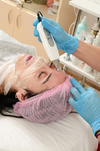 Young woman in beauty salon doing peeling and facial cleansing procedure.
