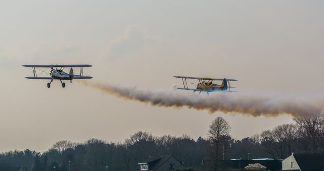 two airplanes taking off with smoking engines, show and stunt planes flying in the sky