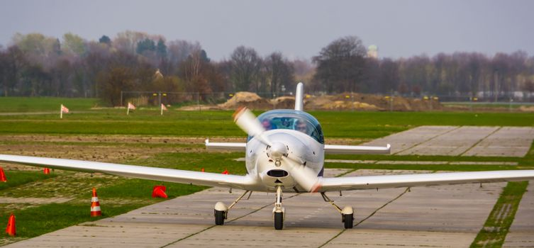 stunt airplane landing on the air strip in closeup, recreational sport and hobby, air transportation background