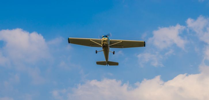 stunt airplane flying in a blue sky with clouds, air transportation, hobby and sports