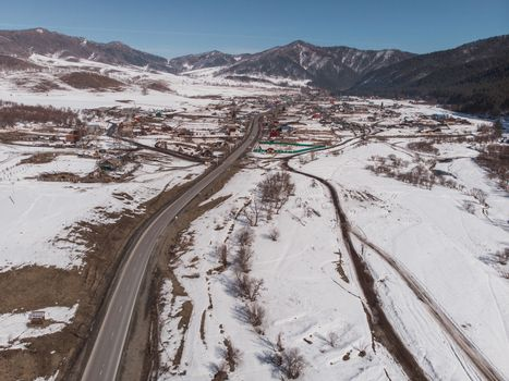 Aerial view of a road in winter landscape of Altai mountains