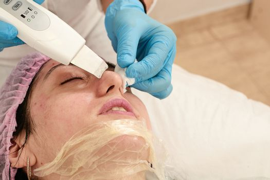 Young woman in beauty salon doing ultrasound peeling and facial cleansing procedure.