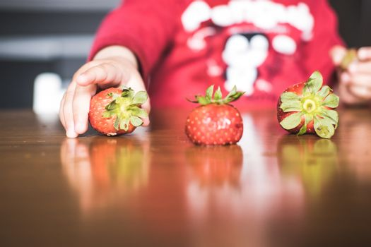 One of the strawberries forming a line on the table is being grabbed by a kid