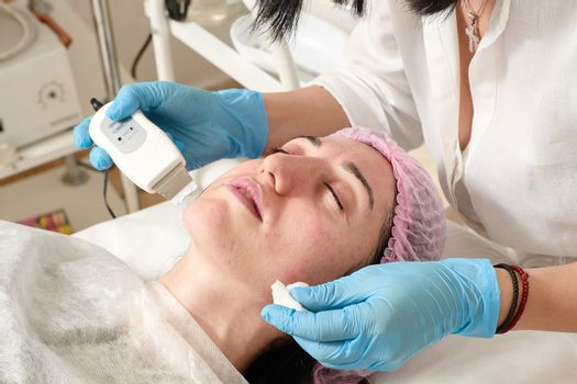 Young woman in beauty salon does ultrasound peeling and facial cleansing procedure.