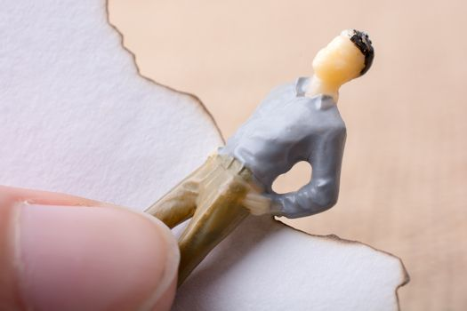 Man figurine held in hand on canvas