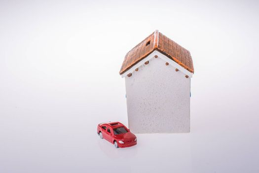 Little model house   and a car on a white background
