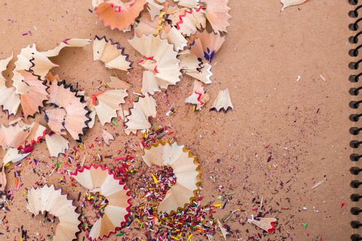 Colorful pencil shavings on a brown background