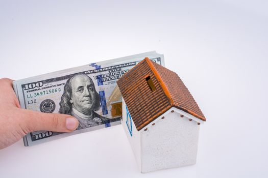 Human hand holding American dollar banknotes by the side of a model house on white background