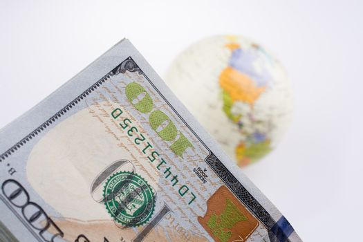 American dollar banknotes by the side of a model globe on white background