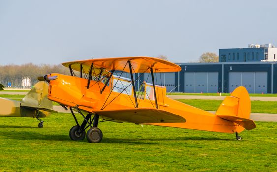 parked orange stunt airplane at the airport, acrobatic flying and extreme hobbies