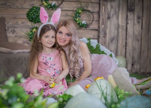 Little child girl wearing bunny ears and her mother among Easter decoration in studio