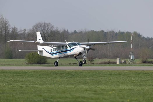Single-engined propeller business plane during take off at a small airport