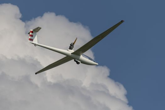 Modern motorized glider in a blue sky with white clouds