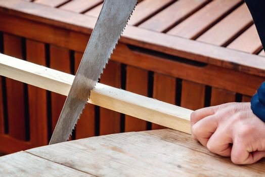 Men's hands sawing a wooden bar with a hacksaw