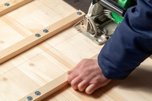 Male hands sawing boards with a circular saw