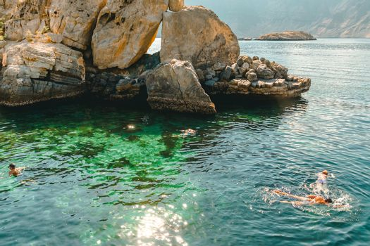 People swim with masks in the clear turquoise water of the Gulf of Oman