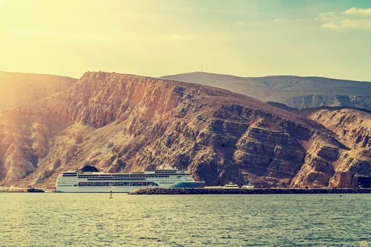Tourist liner at the coast behind a background of rocks in the fjords of the Gulf of Oman