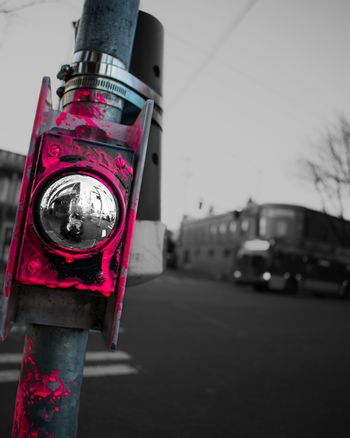 Pink paint on a crosswalk button at a city intersection