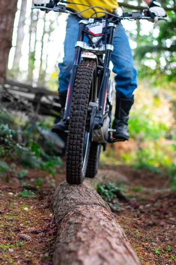 Man riding Motorcycle across log obstacle in the Forest