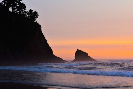 Colorful orange sunset on the beach with rocky coastline outline