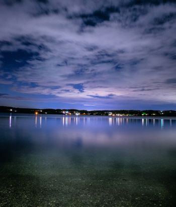 City lights reflecting across the water as night falls