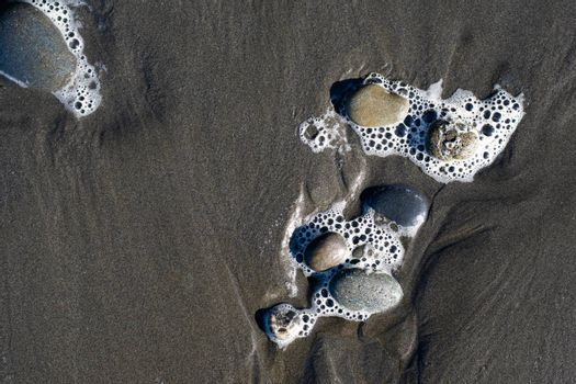 Rocks in foamy sand during low tide