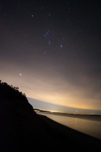 Starry night sky on the coastline with light pollution