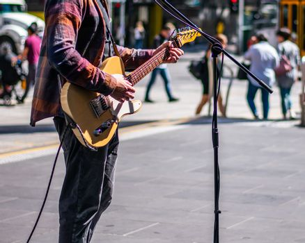 Busker playing guitar on the sidewalk