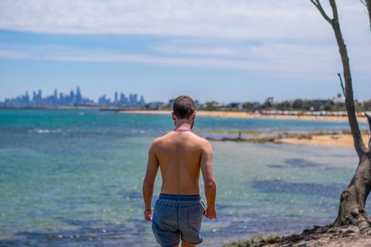 Boy approaching beach on beautiful sunny summer day with city skyline