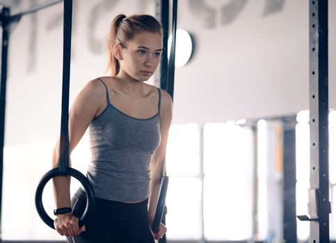 Portrait of Young Sports Woman Training with Gymnastic Rings in the Gym. Fitness and Healthy Lifestyle Concept.
