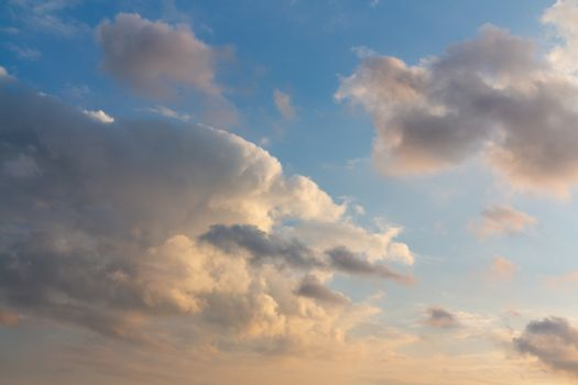 Beautiful cumulus clouds of unusual shape in the blue sky on a summer day