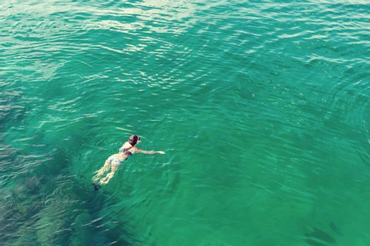 Girl dives with a mask while swimming in the turquoise sea water of the Gulf of Oman