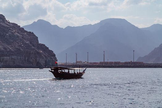 Sea, pleasure boats, rocky shores in the fjords of the Gulf of Oman