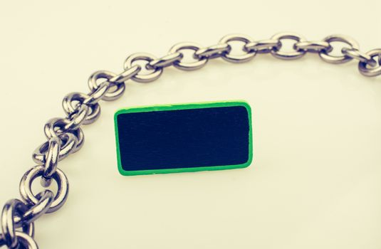Small green sided black noticeboard surrounded by chain on white
