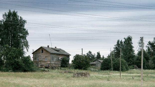 Old wooden house in the meadow. Stone foundation. Rural landscape