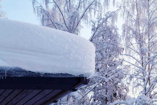 lot of snow on the roof of a rural cottage