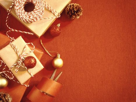 Preparing for the holiday - wrapping Christmas or Christmas gifts in red and beige wrapping paper
