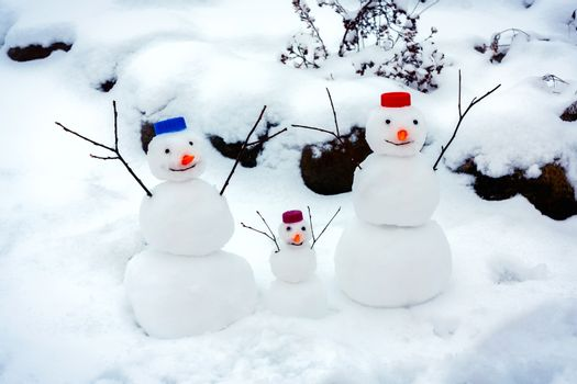 Family of cheerful snowmen rejoice at the arrival of winter and the first snow