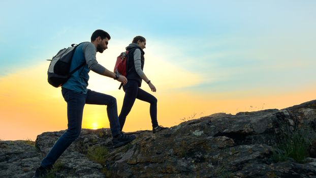 Couple of Young Happy Travelers Hiking with Backpacks on the Beautiful Rocky Trail at Warm Summer Sunset. Family Travel and Adventure Concept.