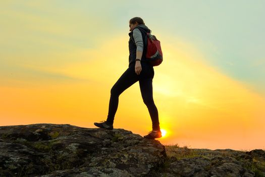 Young Woman Traveler Hiking with Backpack on the Rocky Trail at Warm Summer Sunset. Travel and Adventure Concept.