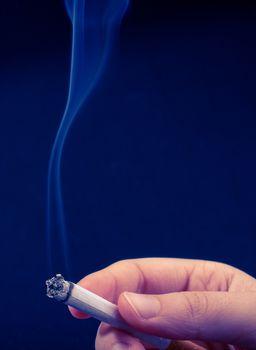 Hand is holding smoking cigarette with smoke around