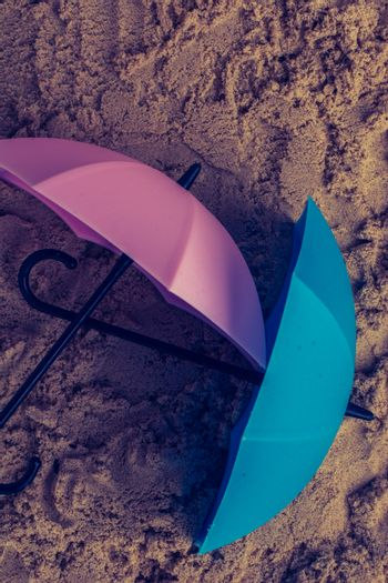 Pink umbrella on sand seen from the top
