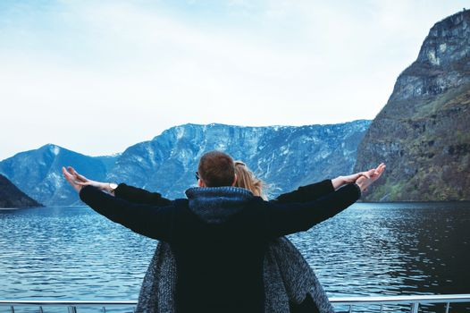Couple travels in Norway. Fjords and mountains. Hands in different directions