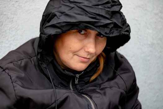 Woman with black hood in a yard