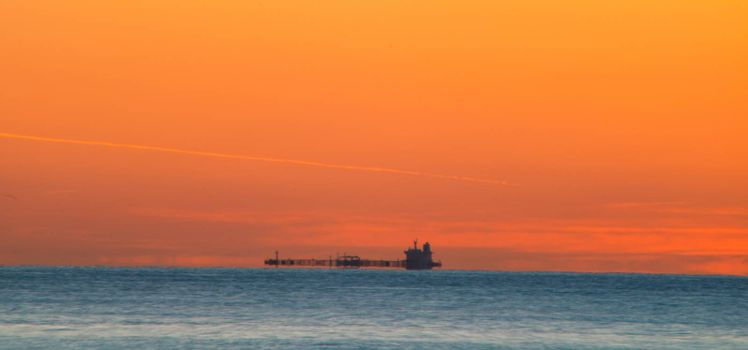 Freighter sailing at sunrise in the Mediterranean Sea