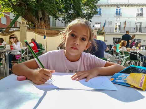 Navajas, Spain 10/12/2018: Little girl drawing in a crowded square