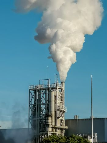 Industrial chimney expelling a lot of smoke over blue sky