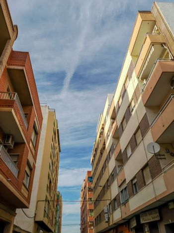 Street with different buildings in the Puerto de Sagunto with cloudy sky